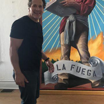 Artist Jay Mercado pictured with his piece La Fuega